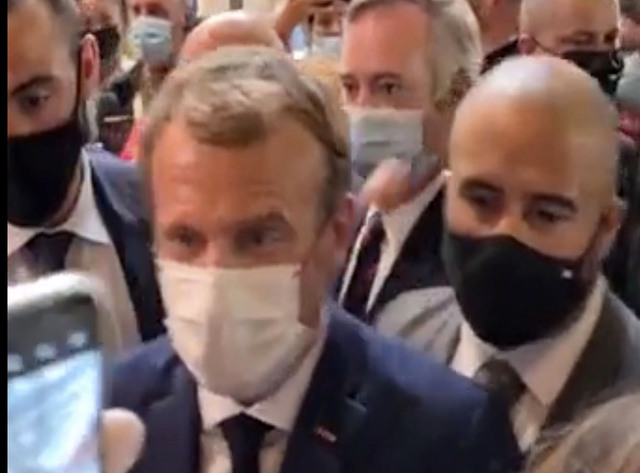 Emmanuel Macron i Lyon rett før egget treffer ham på skulderen. Foto: LYONMAG.COM via AP / NTB