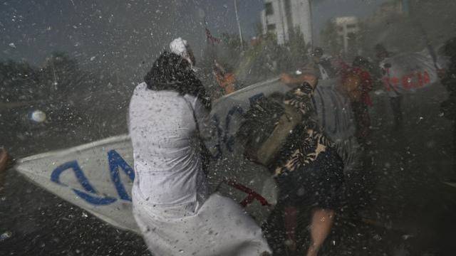 Demonstranter, blant dem en katolsk nonne, presses tilbake av politi med vannkanoner under en demonstrasjon mot ulikhet, to dager før en folkeavstemning om en ny grunnlov i Chile.