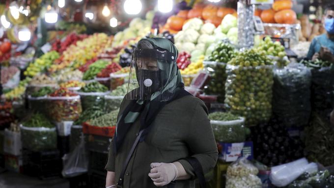 En kvinne i fullt beskyttelsesutstyr på en basar nord i Teheran. Landet opplever en kraftig oppblomstring av koronasmitte.