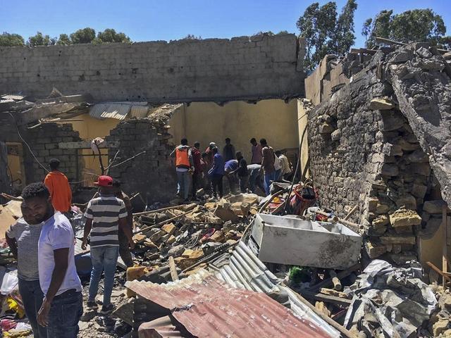 Innbyggere i Mekele går gjennom ruiner etter et luftangrep mot byen torsdag. Foto: AP / NTB