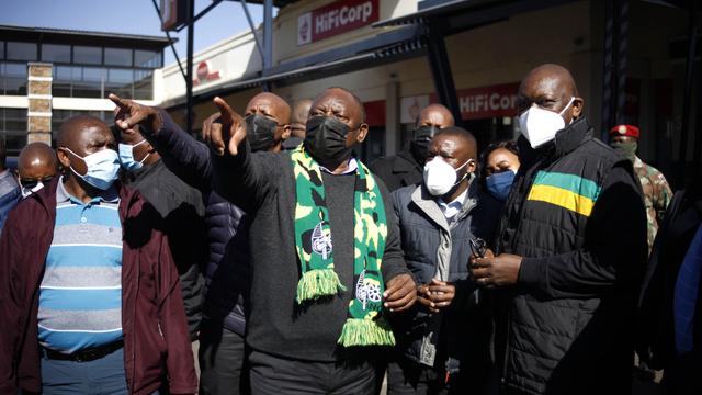 Sør-Afrikas president Cyril Ramaphosa (midten) sier landet har passert toppen på den tredje smittebølgen.