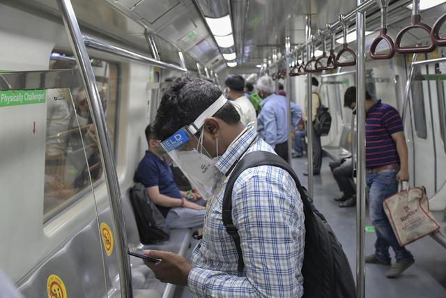 Reisende på metroen i Delhi, som nå får kjøre med halvfulle tog. Foto: Ishant Chauhan / AP / NTB