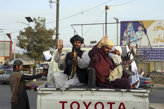 Taliban-krigere vinker fra en pickup i Kabul mandag. En av sjefene i islamistgruppen sier de har skrevet historie, etter at de siste amerikanske soldatene forlot Afghanistan like før midnatt natt til tirsdag. En talsmann for gruppen sier at Afghanistan nå har fått «full uavhengighet». Foto: Khwaja Tawfiq Sediqi / AP / NTB