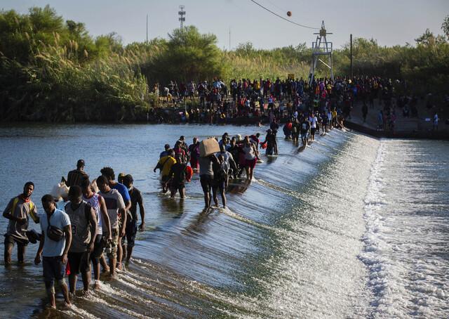 Migranter fra Haiti krysser Rio Grande for å få forsyninger fra amerikansk side av elva. Foto: Marie D. De Jesús / Houston Chronicle via AP / NTB