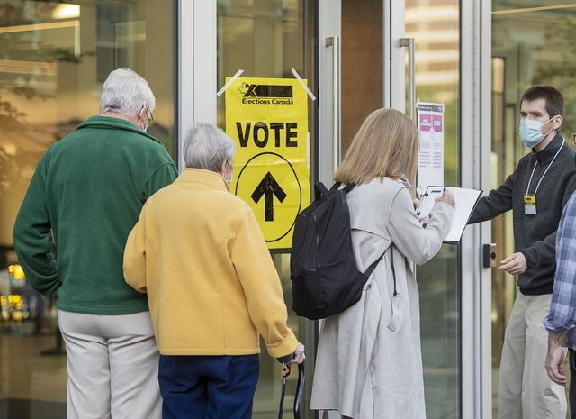 Smittesporing og munnbind sees på dette valglokalet i Halifax Convention Centre i Canada. Mandag kan canadiere stemme. Foto: Andrew Vaughan / The Canadian Press / AP / NTB