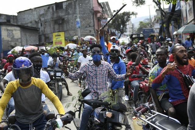 Motorsyklister som ikke kan få tak i bensin, deltar i protester mot Haitis statsminister under en generalstreik i landet. Foto: Matias Delacroix / AP / NTB