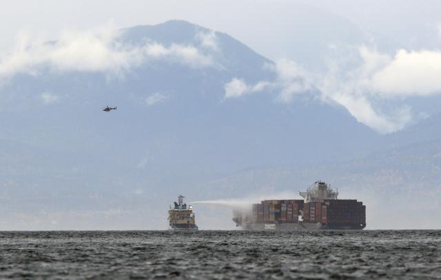 Flere skip deltar i innsatsen for å få kontroll over brannen om bord på MV Zim Kingston, rundt 8 kilometer fra kysten i Victoria i Canada søndag. Foto: THE CANADIAN PRESS/Chad Hipolito/The Canadian Press via AP / NTB