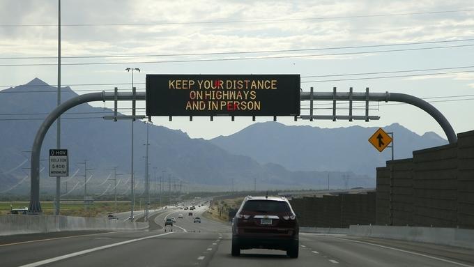 Hold avstand både på veien og mellom personer, heter det i en kunngjøring som henger over en vei i Arizona.