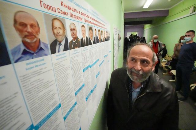 Boris Visjnevskij fra det liberale russiske opposisjonspartiet Yabloko ser på listene over kandidater i et valglokale i St. Petersburg. Han oppdaget at det var to andre menn med samme navn som ham som deltok i valget, en av dem fra regjeringspartiet Forente Russland. Foto: Dmitri Lovetsky / AP /NTB