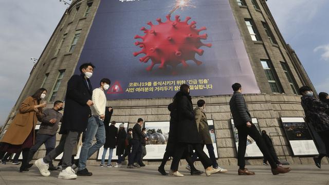 En plakat i Seoul med budskapet «Vi må stoppe opp før covid-19 stopper alt».