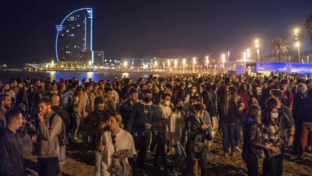 Festglade spanjoler er samlet på en strand i Barcelona for å feire at det går mot mer normale tider.