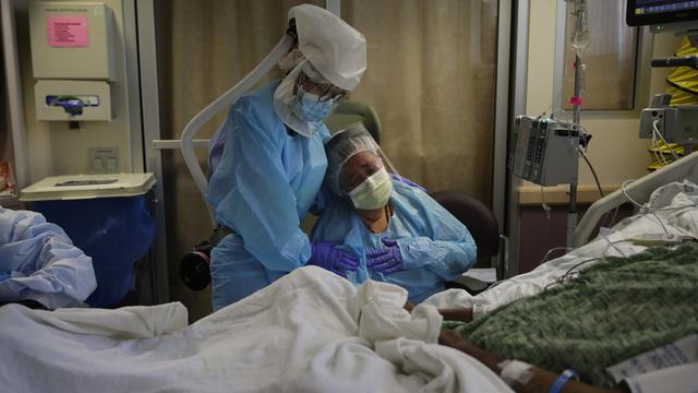 Romelia Navarro (t.h.) fikk trøst av en sykepleier idet ektemannen hennes var i ferd med å dø av covid-19 på et sykehus i Fullerton i California i juli i år.