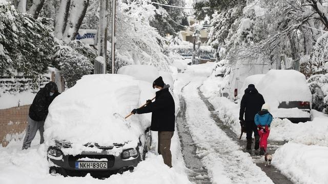 En mann og en gutt i ferd med å fjerne snø fra en bil i en forstad til Aten onsdag i forrige uke.
