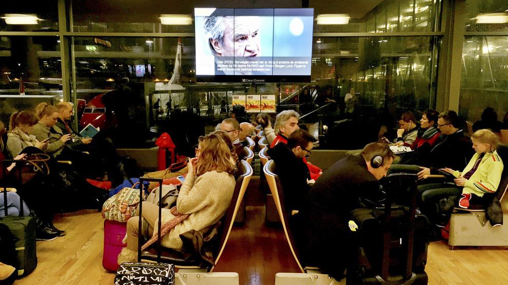 <p><b>KUNDENE MÅ BETALE AVGIFT:</b> Flypassasjerer venter på Oslo lufthavn, mens skjermen bak viser et bilde av Norwegian-sjef Bjørn Kjos.</p>