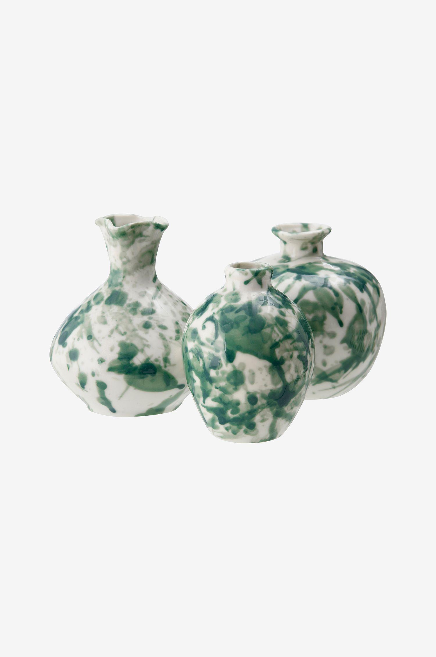 Tre små, grønne og hvite vaser