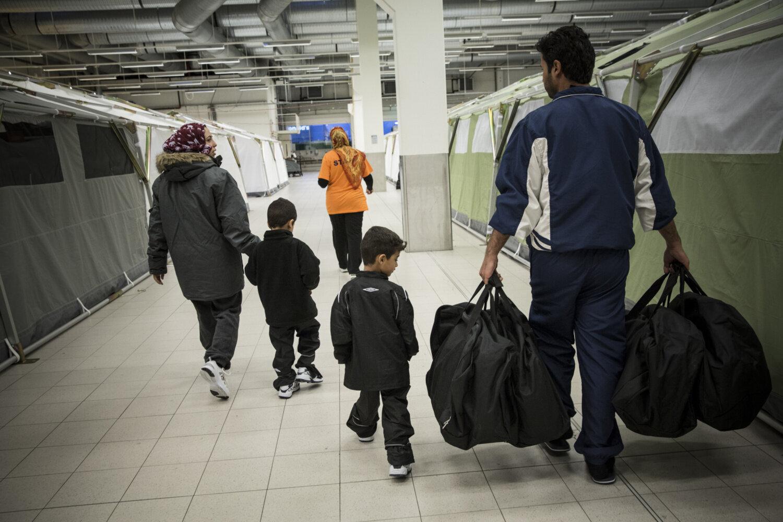 BOR I TELT: Familien har fått utdelt sengetøy og skal til teltene der de skal bo de neste dagene