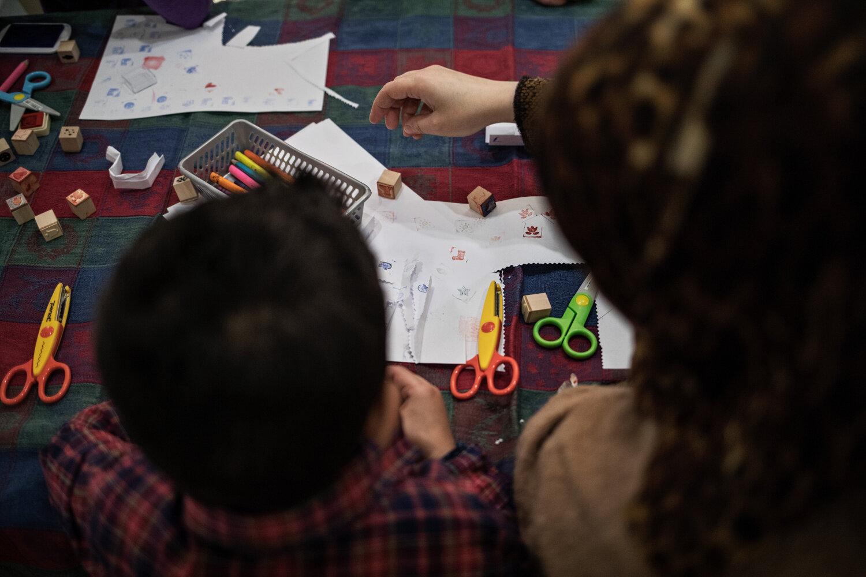 HÅNDARBEID: Akram (6) og moren Daren (6) bruker små stempel til å lage mønster på hvite papirark. Seksåringen har lært seg hva de forskjellige symbolene heter på norsk.