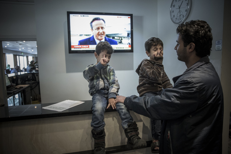 NY VIRKELIGHET: Amer (4) og Akram (5) prøver å få oppmerksomhet fra pappa Lawrence, som ser den britiske statsministeren David Cameron snakke om terrortrusselen på tv.