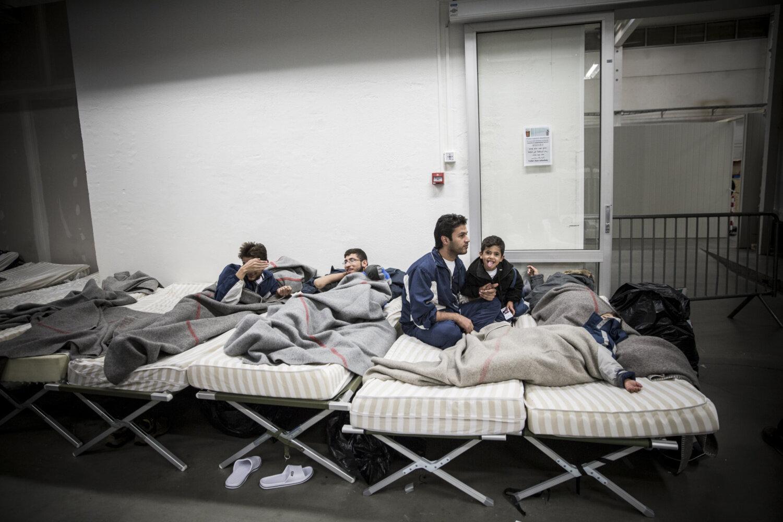 PÅ VENTEROMMET: Lawrence og Akram sitter og prater i senga, mens mamma Daren og minstemann Amer er utslitte etter reisen og sover mens de venter på registrering hos politiet.